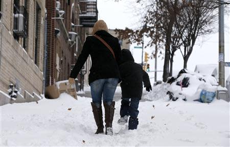 A woman and her son make their way up a snow covered sidewalk in the South Bronx section of New York City, January 3, 2014. REUTERS/Mike Segar