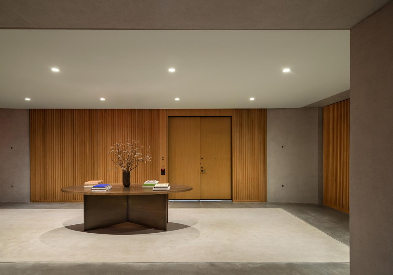 "The building's 15 lofts are accessible through shared foyers, whose decor, emphasizing materiality in concrete and warm wood, sets the tone for the apartments. When looking for a craftsman to create the concrete walls and floors, Rosen immediately thought of Tadao Ando, arguably the master of the medium. Luckily, the well-connected Rosen considers the Japanese architect a friend. ""I called up Tadao and asked him, 'How do you get your concrete so smooth?'"" the developer recalls. ""He told me about these guys, and they flew in a team. They all came in hazmat suits and were so efficient."""