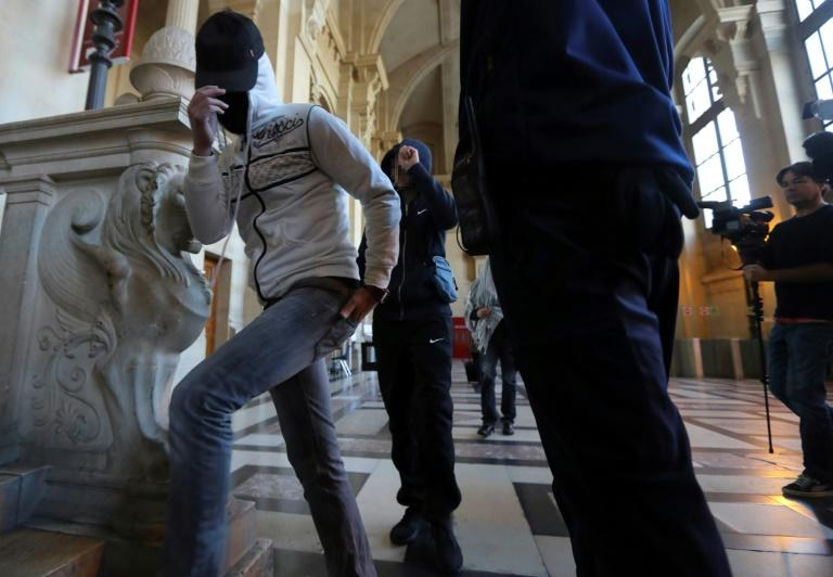 """Witnesses cover their faces as they arrive for the trial of a jihadist network known as the """"Cannes-Torcy cell"""" before a Special Court of Assizes at the Paris courthouse on April 20, 2017"""