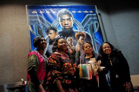 "A group of women pose for a photo in front of a poster advertising the film ""Black Panther"" on its opening night of screenings at the AMC Magic Johnson Harlem 9 cinemas in Manhattan. REUTERS/Andrew Kelly"