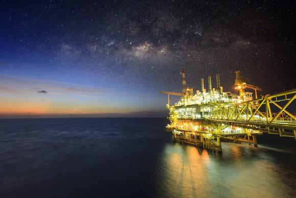 An offshore oil rig with its lights on in open water