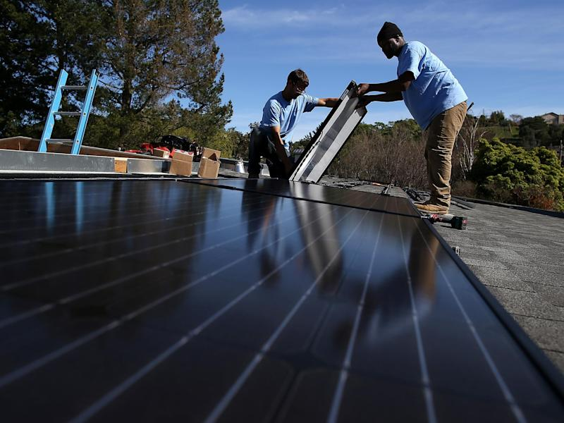 Workers install solar panels on the roof of a home in San Rafael, California: Getty