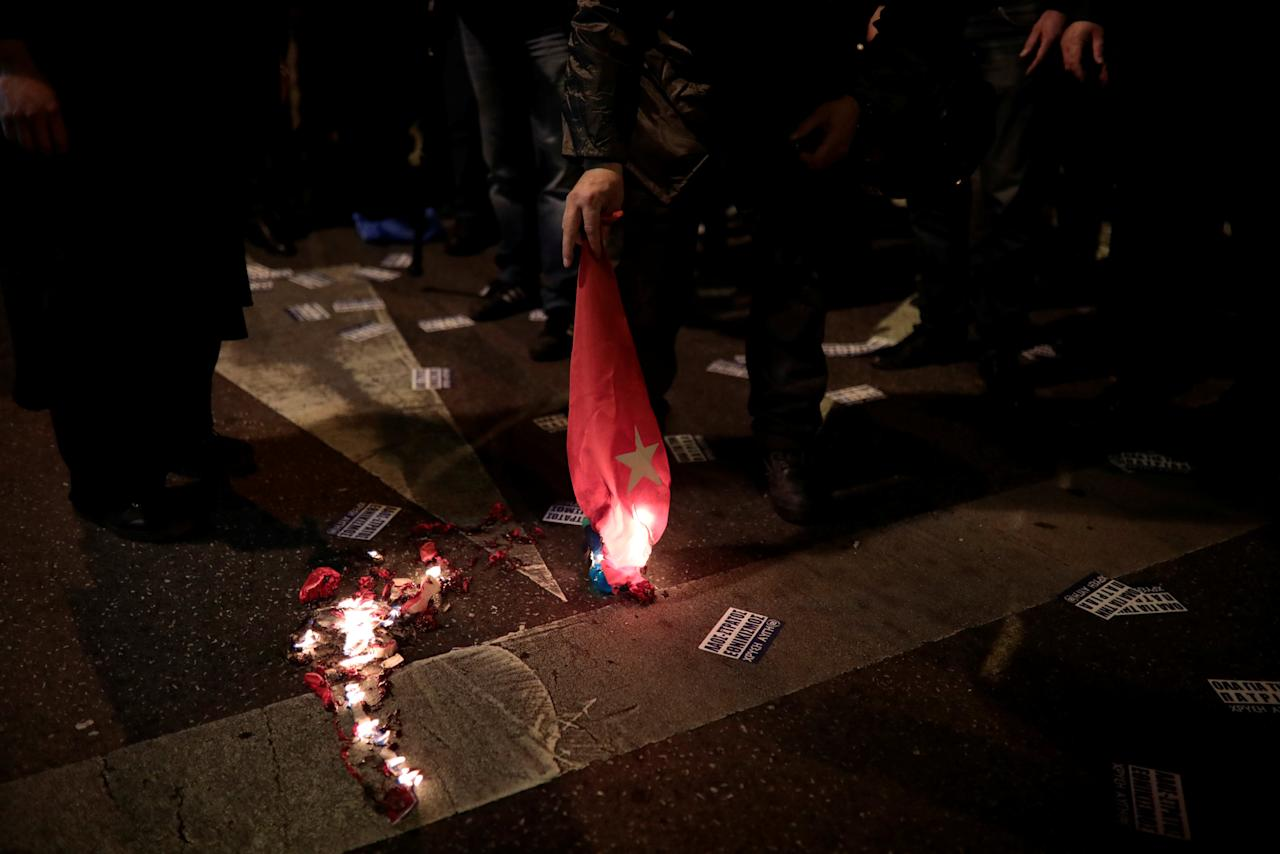 A supporter of Greece's far-right Golden Dawn party burns  a Turkish national flag during a protest against Turkey in Athens, Greece, March 5, 2018. REUTERS/Alkis Konstantinidis