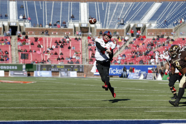 FILE- In this Dec. 30, 2019, file photo, a lot of seats are unoccupied as Western Kentucky quarterback Ty Storey (4) throws a pass during the second half of the NCAA First Responder Bowl college football game against Western Michigan in Dallas. Bowls outside the College Football Playoff structure might excite only the most ardent fans of the participating teams, be played in half-empty stadiums and prompt howls about there being too many games. They aren't going away, though. There'll be three more next season, bringing the total number of bowls to 42. (AP Photo/Roger Steinman, File)
