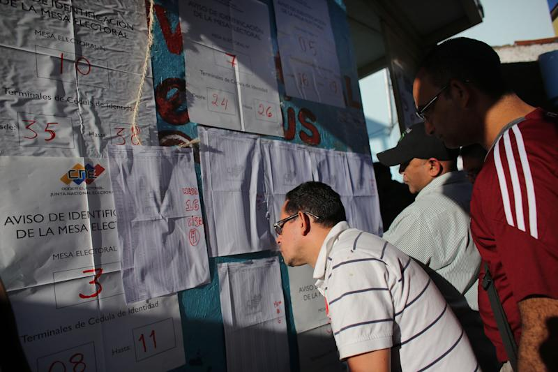 Residents search their name on the voters list outside of a polling station during municipal elections in Caracas, Venezuela, Sunday, Dec. 8, 2013. Venezuelans head to the polls to elect mayors and city councilors at a moment when the country's economic troubles have deepened, with inflation touching a two-decade high of 54 percent, and shortages of everything from toilet paper to milk spreading while the black market value of the currency plunges. (AP Photo/Ariana Cubillos)