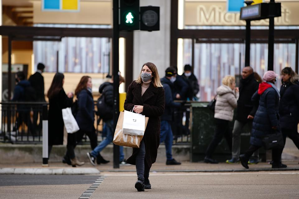 A shopper wearing a face mask crosses Oxford Circus in London, England, on December 4, 2020. London has returned to so-called Tier 2 or 'high alert' coronavirus restrictions since the end of the four-week, England-wide lockdown on Wednesday, meaning a reopening of non-essential shops and hospitality businesses as the festive season gets underway. Rules under all three of England's tiers have been strengthened from before the November lockdown, however, with pubs and restaurants most severely impacted. In London's West End, Oxford Street and Regent Street were both busy with Christmas shoppers this afternoon, meanwhile, with the retail sector hoping for a strong end to one of its most difficult years. (Photo by David Cliff/NurPhoto via Getty Images)
