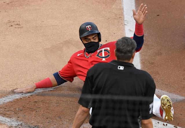 "A masked <a class=""link rapid-noclick-resp"" href=""/mlb/players/7681/"" data-ylk=""slk:Nelson Cruz"">Nelson Cruz</a> and the Minnesota Twins played Friday night even though positive COVID-19 tests on the St. Louis Cardinals, a recent opponent, through their day into question. (Photo by Hannah Foslien/Getty Images)"