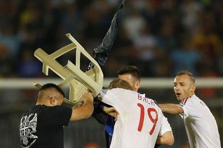 A fan of Serbia scuffles with Bekim Balaj (C) of Albania next to his teammate Ansi Agolli (R) and Nenad Tomovic of Serbia during their Euro 2016 Group I qualifying soccer match at the FK Partizan stadium in Belgrade October 14, 2014. REUTERS/Marko Djurica