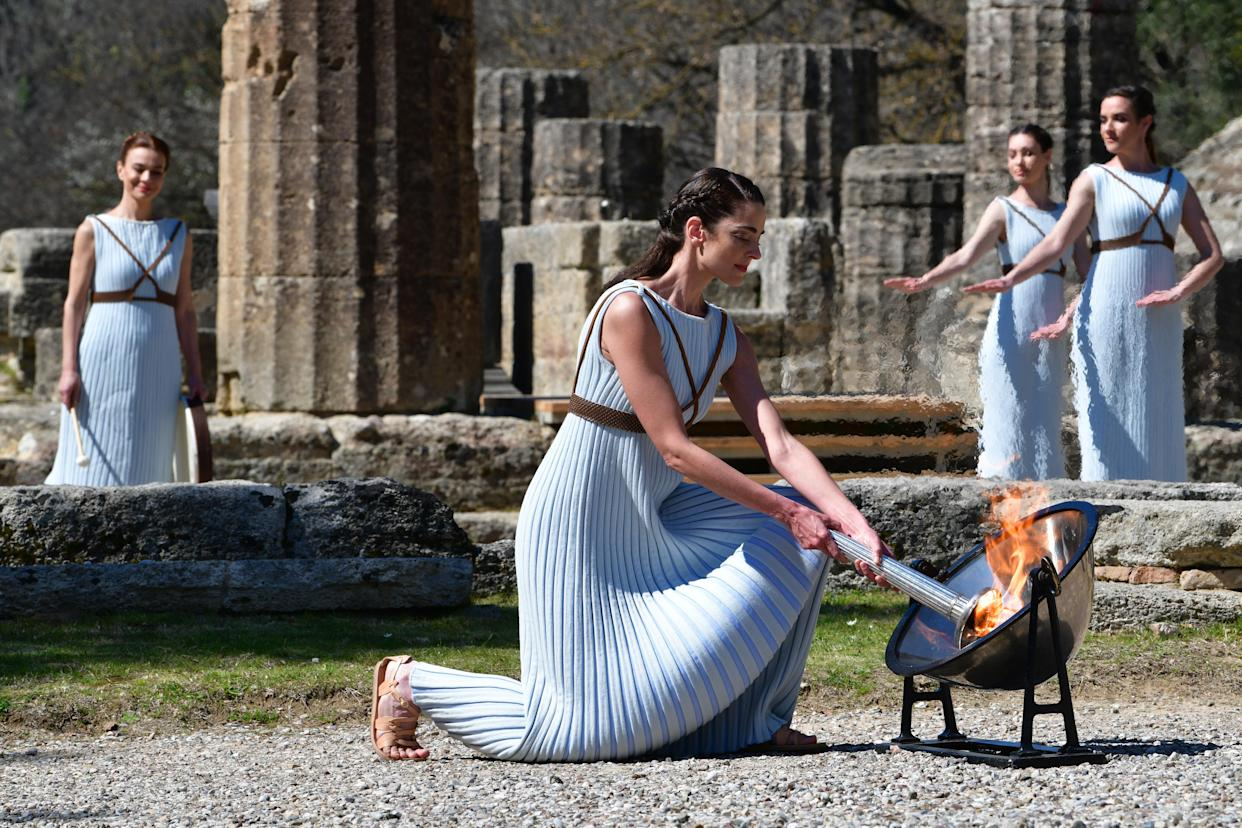OLYMPIA, GREECE - MARCH 12: Greek actress Xanthi Georgiou in the role of the High Priestess lights the torch of the Olympic Flame during the Lighting Ceremonyâ of the Olympic Flame for the Tokyo Summer Olympics, at the Temple of Hera in Ancient Olympia, Greece, on 12 March 2020. (Photo by Antonis Nikolopoulos/Anadolu Agency via Getty Images)
