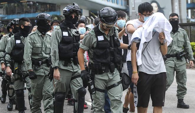 Protesters emerge from the surrounded Polytechnic University and are escorted away by police. Photo: K.Y. Cheng