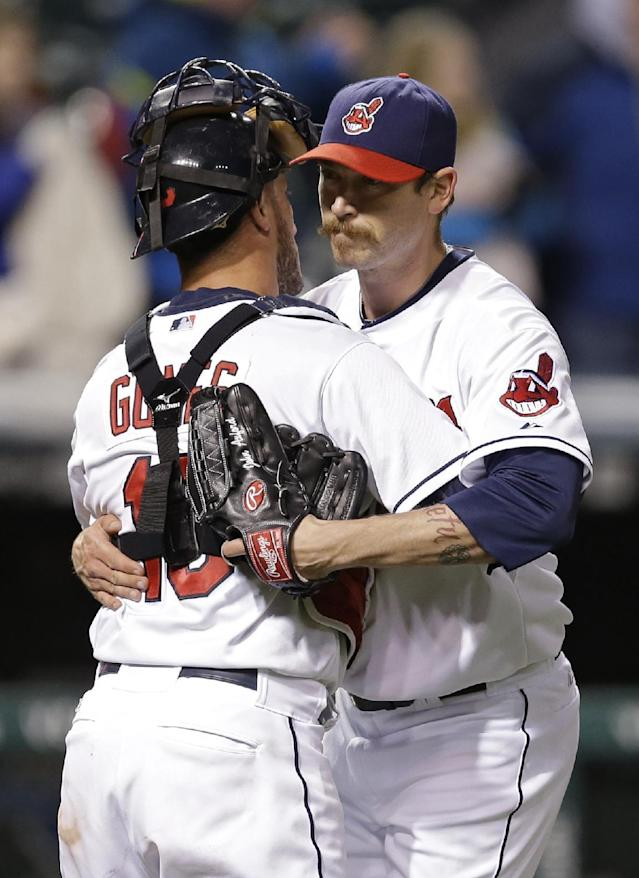 Cleveland Indians relief pitcher John Axford, right, and catcher Yan Gomes hug after Axford got the save in a 5-3 win over the Kansas City Royals in a baseball game Wednesday, April 23, 2014, in Cleveland. (AP Photo/Mark Duncan)
