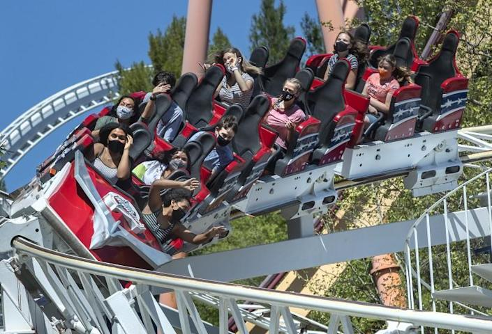 VALENCIA, CA - APRIL 02, 2021: People ride the Revolution roller coaster, the world's first looping roller coaster, at Six Flags Magic Mountain in Valencia on the second day that the park re-opened after more than a year of being closed due to the coronavirus outbreak. In order to maintain social distancing, every other row was kept empty. The only exception was for members of the same family who were allowed to sit in two rows right next to each other. (Mel Melcon / Los Angeles Times)