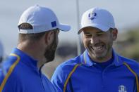 Team Europe's Sergio Garcia smiles with teammate Team Europe's Jon Rahm during a foursome match the Ryder Cup at the Whistling Straits Golf Course Friday, Sept. 24, 2021, in Sheboygan, Wis. (AP Photo/Ashley Landis)
