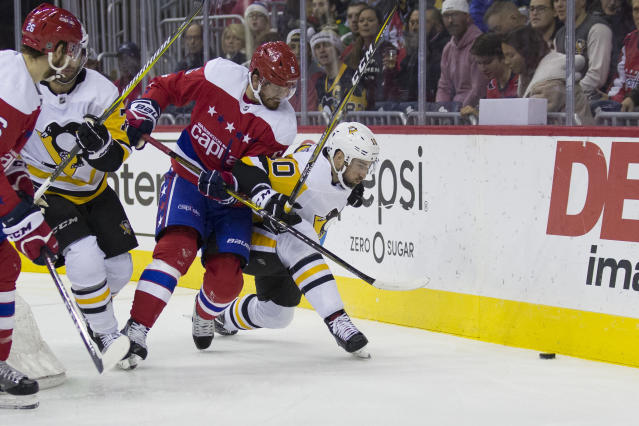 Washington Capitals defenseman Michal Kempny (6), from the Czech Republic, and Pittsburgh Penguins left wing Garrett Wilson (10) battle for the puck in the first period of an NHL hockey game, Wednesday, Dec. 19, 2018, in Washington. (AP Photo/Alex Brandon)