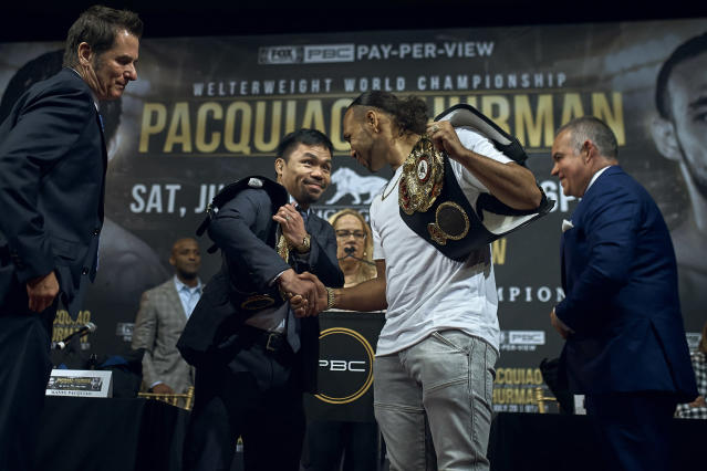 Manny Pacquiao, center left, shakes hands with Keith Thurman, center right, during a news conference Tuesday, May 21, 2019, in New York. The two are scheduled to fight in a welterweight world championship bout on Saturday, July 20, in Las Vegas. (AP Photo/Andres Kudacki)