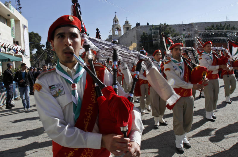 Palestinian scouts play bagpipes in Manger Square, outside the Church of Nativity, traditionally believed by Christians to be the birthplace of Jesus Christ, during a Christmas parade in the West Bank town of Bethlehem, Friday, Dec. 24, 2010.(AP Photo/Adel Hana)
