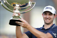 Patrick Cantlay holds up the trophy after winning the Tour Championship golf tournament and the FedEx Cup at East Lake Golf Club, Sunday, Sept. 5, 2021, in Atlanta. (AP Photo/Brynn Anderson)