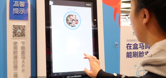 A Hema supermarket customer taps on a screen as she pays for her items using facial-recognition technology