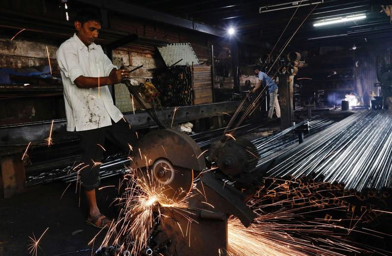 Workers make pipes used for drilling, at a factory in an industrial area in Mumbai