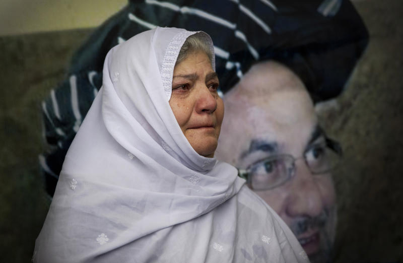 Humera Ehmedzai, a colleague of slain Afghan governor Arsallah Jamal, who's picture is on the wall behind her, cries at his funeral ceremony at the Eid Gha mosque in Kabul, Afghanistan, Thursday, Oct 17, 2013. Afghan officials, dignitaries and family members attended the funeral of the governor of eastern Logar province, who was killed in an insurgent attack earlier this week. (AP Photo/Anja Niedringhaus)