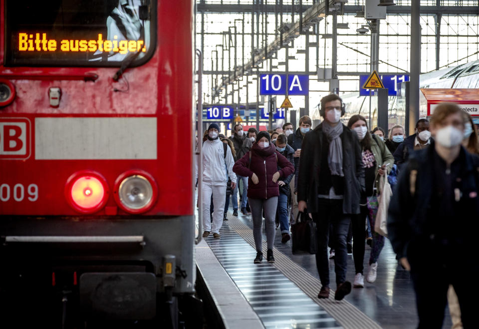 """Commuters wearing face masks walk on a platform in the main train station in Frankfurt, Germany, Tuesday, March 2, 2021. German politics discusses further steps to avoid the outspread of the coronavirus. Letters an train read """"please disembark"""". (AP Photo/Michael Probst)"""