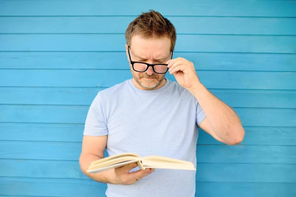 Portrait of mature man with big black eye glasses trying to read book but having difficulties seeing text because of vision problems. Problems disorder vision. - Image