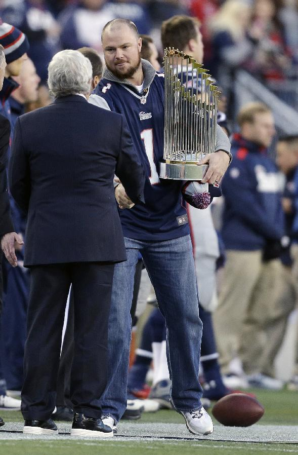 Boston Red Sox Pitcher John Lester, right, shakes hands with New England Patriots owner Robert Kraft as he carries the World Series trophy onto the field before an NFL football game between the Patriots and the Pittsburgh Steelers Sunday, Nov. 3, 2013, in Foxborough, Mass. (AP Photo/Steven Senne)