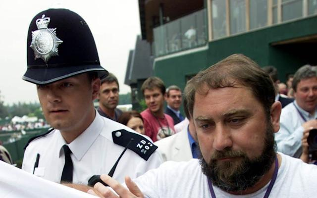 Damir Dokic (right), father of Australian tennis player Jelena Dokic is escorted by the police from the media balcony at Wimbledon today, Thursday 29th June 2000 following an incident with Sky TV reporter Mark Saggers in which Dokic appeared to smash Saggers mobile phone