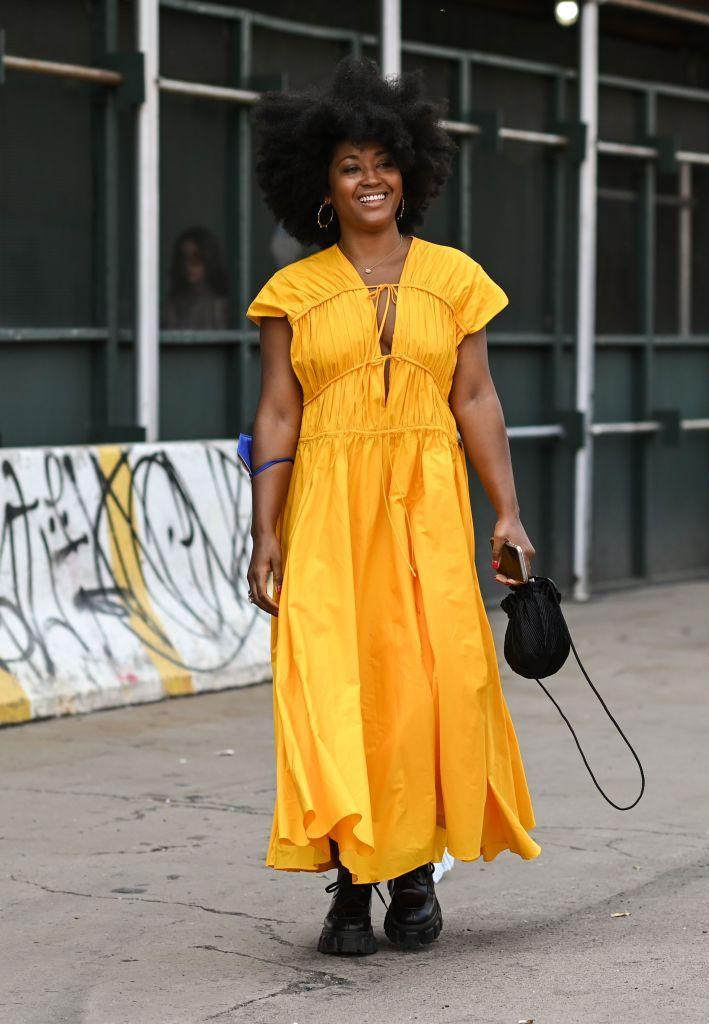 <p>This guest paired Prada boots with Tove's sunshine yellow dress for NYFW.</p>