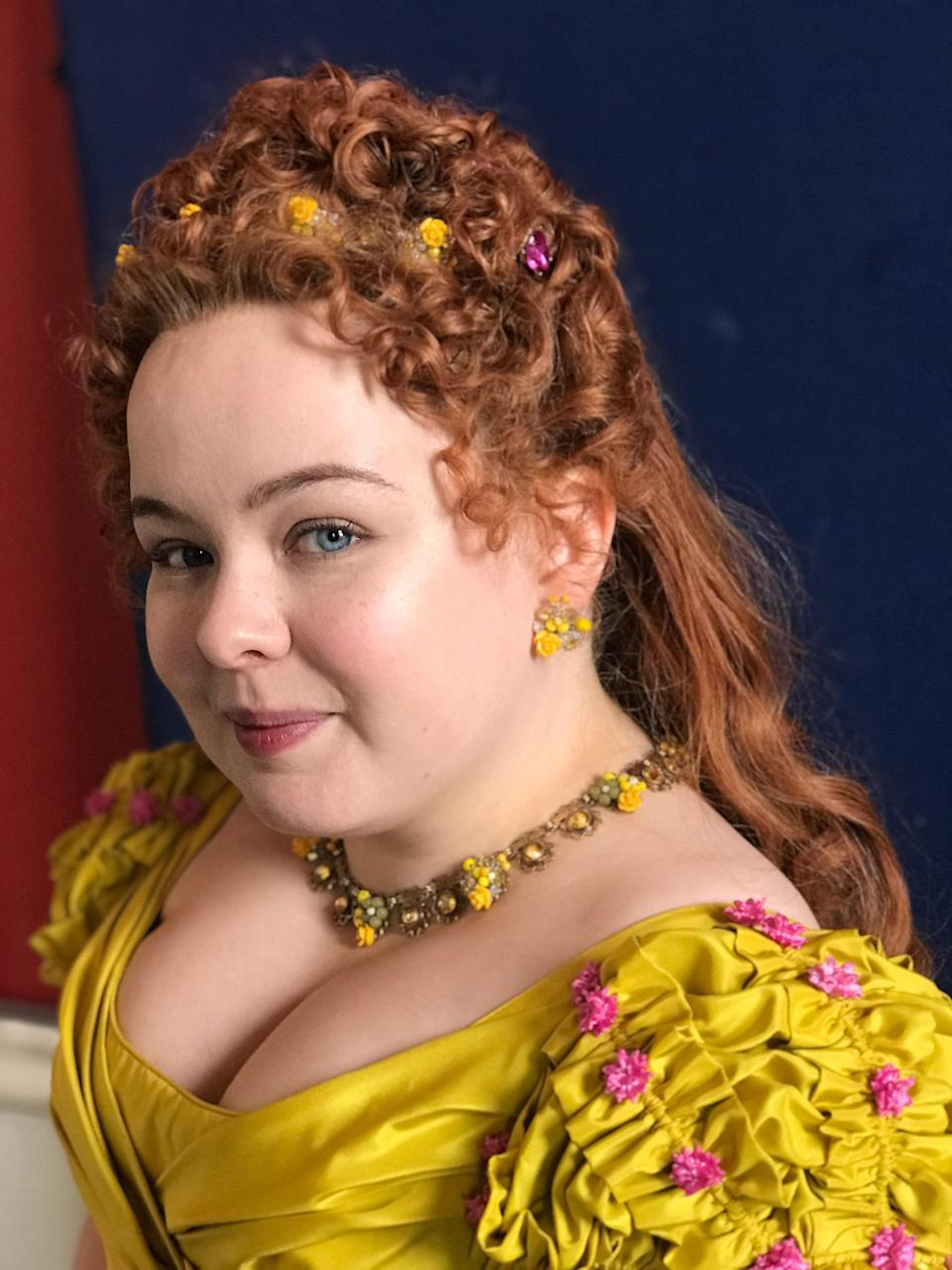 An up-close look at Nicola Coughlin's mustard yellow gown with pink floral accents. In addition to Glaser, John Norster and Ellen Mirojnick are also costume designers on the series.