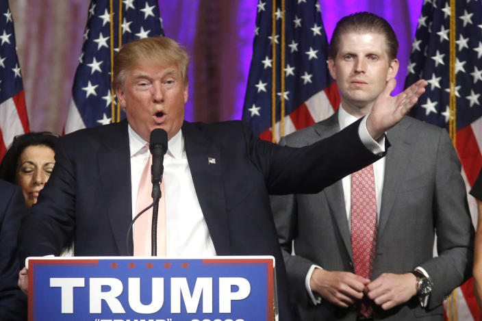 "FILE - In this Tuesday, March 15, 2016, file photo, Republican presidential candidate Donald Trump speaks to supporters at his primary election night event at his Mar-a-Lago Club in Palm Beach, Fla. At right is his son Eric Trump. Hits to President Donald Trump's business empire since the deadly riots at the U.S. Capitol are part of a liberal ""cancel culture,"" his son Eric told The Associated Press on Tuesday, Jan. 12, 2021, saying his father will leave the presidency with a powerful brand backed by millions of voters who will follow him ""to the ends of the Earth."" (AP Photo/Gerald Herbert, File)"