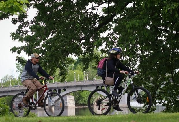 A pair of cyclists make their way along a trail in Kingsview Park in Ottawa's Vanier community on May 28, 2021.