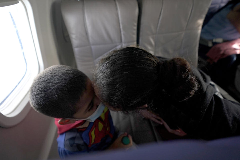 Celestina Ramirez, right, a migrant from Honduras, kisses her son Yancarlos Amaya, 5, while riding on an airplane to Houston, Wednesday, March 24, 2021, in Harlingen, Texas. The mother and son, who are headed to Baltimore to reunite with Ramirez's brother, were granted to stay in the U.S. after turning themselves to U.S. (AP Photo/Julio Cortez)