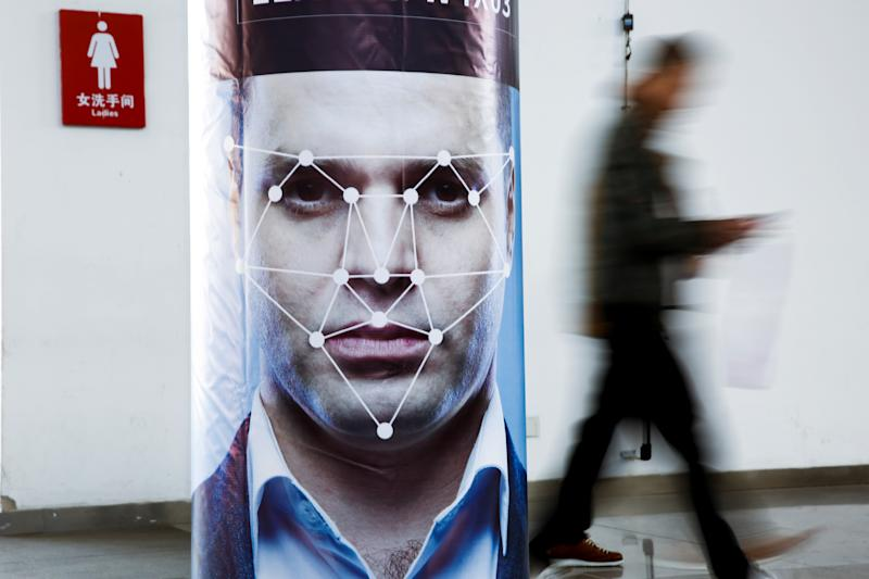 A man walks past a poster simulating facial recognition software in Beijing, China (REUTERS/Thomas Peter)