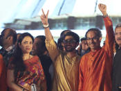 Shiv Sena party leader Uddhav Thackeray, right, as his wife Rashmi and son Aaditya Thackeray stand with him after he took oath as chief minister of Maharashtra state during a swearing-in-ceremony in Mumbai, Thursday, Nov. 28, 2019. Supporters of the Shiv Sena, Nationalist Congress Party (NCP) and the Congress party thronged Shivaji Park to watch their leaders take oath of office. (AP Photo/Rafiq Maqbool)