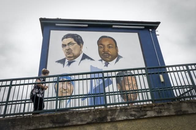 A woman walks past the Bogside mural in Derry City of John Hume, Martin Luther King Jr, Mother Teresa, and Nelson Mandela (Liam McBurney/PA)