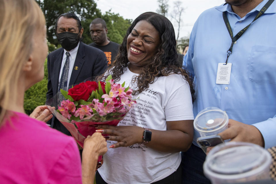 Rep. Cori Bush, D-Mo., reacts to receiving flowers after it was announced that the Biden administration will enact a targeted nationwide eviction moratorium outside of Capitol Hill in Washington on Tuesday, August 3, 2021. For the past five days, lawmakers and activists primarily led by Bush have been sitting in on the steps of Capitol Hill to protest the expiration of the eviction moratorium. (AP Photo/Amanda Andrade-Rhoades)