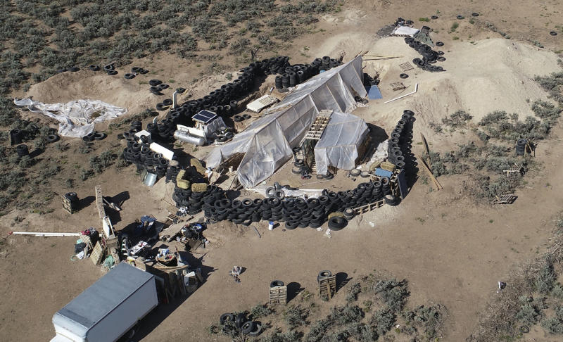 FILE - This Aug. 10, 2018, file photo shows a ramshackle compound in the desert area of Amalia, N.M. A federal judge has ordered a woman charged with kidnapping, firearm and terrorism-related counts to be hospitalized, saying she suffers from mental illness. The decision Thursday, Oct. 17, 2019, orders up to four months of hospitalization for Jany Leveille, with plans to reevaluate later whether she might be competent to stand trial. (AP Photo/Brian Skoloff, File)