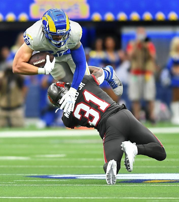Rams tight end Tyler Higbee is upended by Buccaneers safety Antoine Winfield.