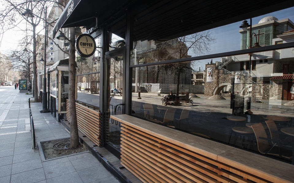 People sitting on benches in a usually crowded street are reflected in the window of a closed restaurant in downtown Skopje, North Macedonia, Wednesday, March 18, 2020. While expecting the President to declare the state of emergency, North Macedonia has closed borders for foreign nationals to enter, shut down two country's airports, restaurants, bars, schools, universities, kindergartens and constantly appeal people to stay at home to slow the spread of the coronavirus outbreak. For most people, the new coronavirus causes only mild or moderate symptoms. For some it can cause more severe illness, especially in older adults and people with existing health problems. (AP Photo/Boris Grdanoski)