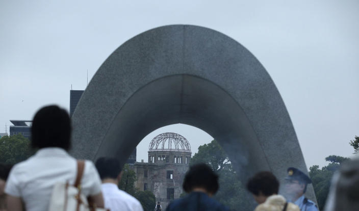 People pray for the atomic bomb victims in front of the cenotaph at the Hiroshima Peace Memorial Park in Hiroshima, western Japan, Tuesday, Aug. 6, 2013. Japan marked the 68th anniversary Tuesday of the atomic bombing of Hiroshima with pledges to seek to eliminate nuclear weapons. (AP Photo/Shizuo Kambayashi)