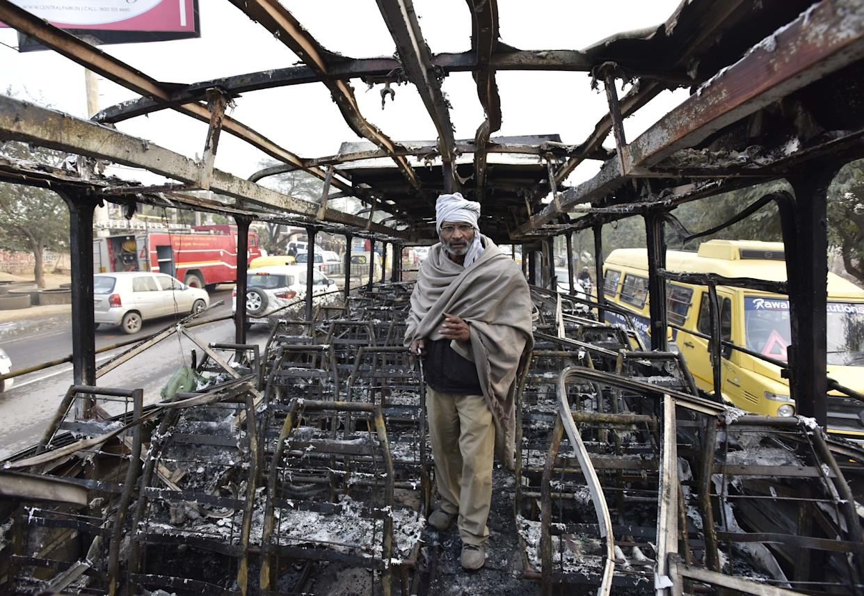 """Abus conductorstands inside a bus that was set on fire near the village of Bhondsi in Gurgaon, allegedly by activists of Karni Sena, who were protesting against the release of film """"Padmaavat."""" (Photo: Hindustan Times via Getty Images)"""