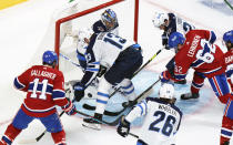 CORRECTS PHOTOGRAPHER TO PAUL CHIASSON INSTEAD OF RYAN REMIORZ - Montreal Canadiens' Artturi Lehkonen scores past Winnipeg Jets goaltender Connor Hellebuyck as Jets' Pierre-Luc Dubois(13) and Derek Forbort(24) try to defend during the second period of an NHL Stanley Cup playoff hockey game in Montreal, Sunday, June 6, 2021. (Paul Chiasson/The Canadian Press via AP)