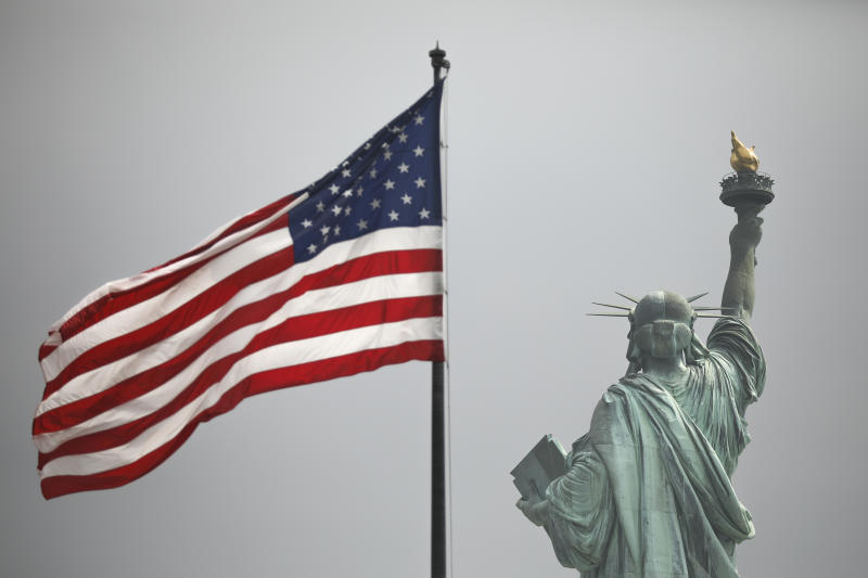 NEW YORK, NY - AUGUST 14: An America flag flies near the Statue of Liberty on Liberty Island on August 14, 2019 in New York City. On Tuesday, acting Director of the Citizenship and Immigration Services Ken Cuccinelli reworked the words of the Emma Lazarus poem The New Colossus as he defended the Trump administrations immigration policies. The poem appears on a plaque inside The Statue of Liberty. The 1883 poem by Lazarus is often cited as an inspiration statement about Americas attitude toward immigrants. (Photo by Drew Angerer/Getty Images)