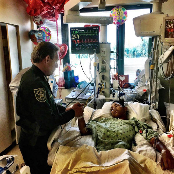FILE - This file image made available by the Broward County Sheriff's Office on Sunday, Feb. 18, 2018, shows Sheriff Scott Israel, holding the hand of Anthony Borges, 15, a student at Marjory Stoneman Douglas High School. Borges, credited with saving his classmates' lives by using his body to block a door during the Florida school shooting that killed 17, left the hospital Wednesday, April 4, after nine surgeries, the Sun Sentinel reports. (Broward County Sheriff's Office via AP, File)