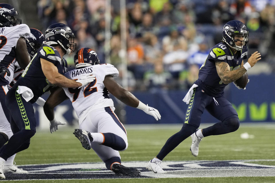 Seattle Seahawks quarterback Alex McGough, right, scrambles with the ball during the first half of the team's NFL preseason football game against the Denver Broncos, Saturday, Aug. 21, 2021, in Seattle. (AP Photo/Stephen Brashear)