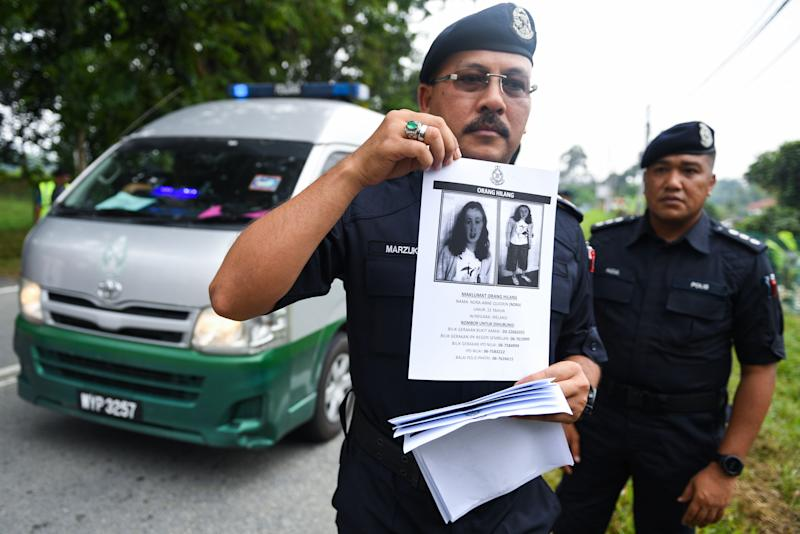 A Royal Malaysian Police officer holds a leaflet bearing a portrait of the missing 15-year-old Franco-Irish girl Nora Quoirin at a checkpoint during a search and rescue operation in Seremban on August 9, 2019. - Malaysian officials played recordings of a Franco-Irish teen's mother over megaphones on August 9 the sixth day of a desperate hunt for the schoolgirl who disappeared from a rainforest resort, police said. (Photo by Mohd RASFAN / AFP) (Photo credit should read MOHD RASFAN/AFP/Getty Images)
