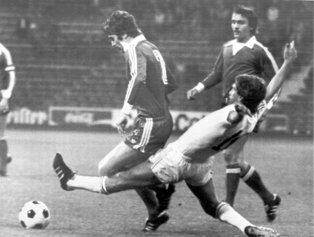 -FILE- In this August 17, 1976, file image, Anderlecht player Rob Rensenbrink, right, stretches to push the ball away during the Super Cup soccer match between FC Bayern Munich and RSC Anderlecht, in Munich, Germany. Behind Rensenbrink are FC Bayern players Rainer Kuenkel and Udo Horsmann. Rensenbrink, the forward who was centimeters away from delivering the Netherlands a World Cup title in 1978 has died at age 72, the Dutch football association said Saturday, Jan. 25, 2020. (AP Photo/D. Hampe, File)