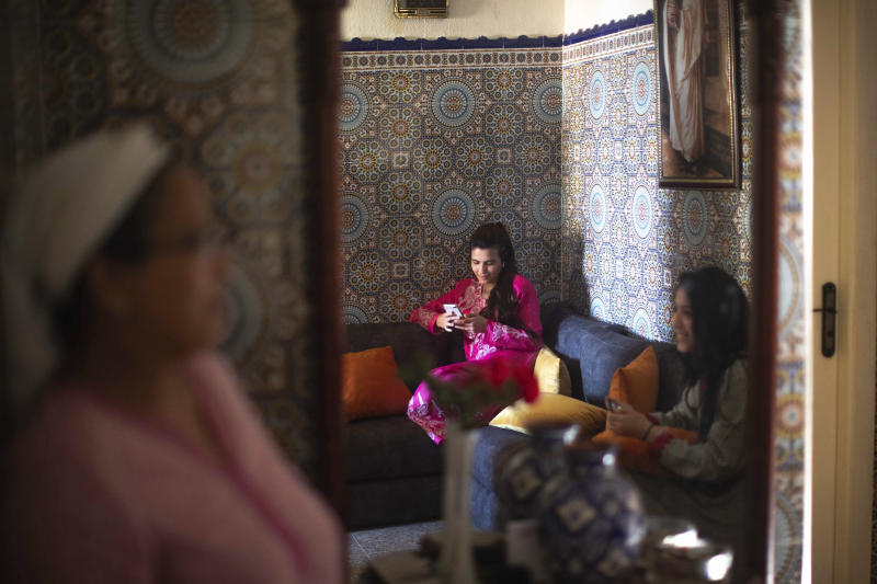 Family members Zineb Jammar, center, and Fadila Lahta, right, use their electronic devices as they spend the first day of Eid in lockdown due to the Coronavirus pandemic, in Sale, Morocco, Sunday, May 24, 2020. (AP Photo/Mosa'ab Elshamy)