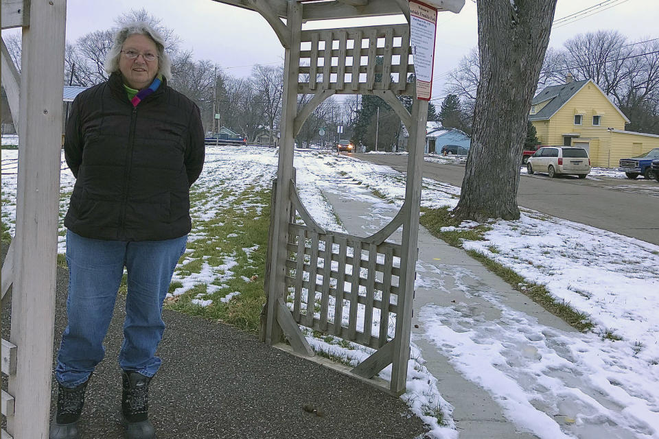 Edna Sabucco, stands near her house in Flint, Mich. Tuesday, Jan. 12, 2021. Former Michigan Gov. Rick Snyder, top aide Rich Baird and his health director Nick Lyon have been told they will face charges resulting from the Flint water crisis, according to a source with knowledge of the situation. Sabucco said she still uses water filters, although the lead service line at her home of 40-plus years has been replaced, along with more than 9,700 others in Flint. (AP Photo/Tammy Webber)